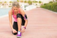 Mujer apta que ata el zapato de los deportes antes de ejercicio de la mañana Imágenes de archivo libres de regalías