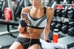 Mujer apta que descansa sobre banco en el gimnasio que escucha la música imágenes de archivo libres de regalías