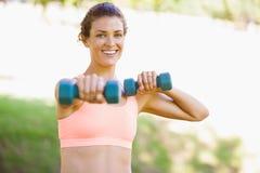 Mujer apta que ejercita con pesas de gimnasia en el parque Fotografía de archivo