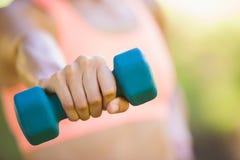 Mujer apta que ejercita con pesas de gimnasia en el parque Imagenes de archivo