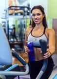 Mujer apta que ejercita en el entrenamiento elíptico del instructor del caminante de los aeróbicos del gimnasio de la aptitud Imágenes de archivo libres de regalías