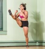 Mujer apta que golpea con el pie arriba Imagen de archivo libre de regalías