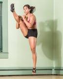Mujer apta que golpea con el pie con salto Imagen de archivo