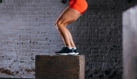 Mujer apta que hace ejercicio del salto de la caja La mujer muscular que hace la caja salta en el gimnasio Foto de archivo libre de regalías