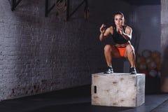 Mujer apta que hace ejercicio del salto de la caja La mujer muscular que hace la caja salta en el gimnasio Imagen de archivo libre de regalías
