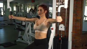 Mujer apta que hace ejercicio en pecho metrajes