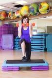 Mujer apta que hace ejercicios con pesas de gimnasia en un tablero del paso Imagenes de archivo