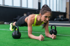 Mujer apta que hace el ejercicio del tablón que trabaja en los músculos abdominales en el gimnasio Imagen de archivo