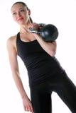 Mujer apta que lleva a cabo un kettlebell en la posición del estante Foto de archivo libre de regalías