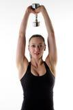 Mujer apta que lleva a cabo una sola pesa de gimnasia de arriba Imagenes de archivo