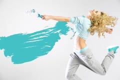 Mujer apta que pinta las paredes vacías Imagenes de archivo
