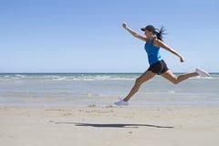 Mujer apta que salta el mediados de aire en una playa Foto de archivo