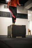 Mujer apta que salta en la caja del gimnasio para el entrenamiento imagenes de archivo