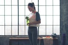 Mujer apta que se coloca en perfil en el gimnasio del desván que sostiene la botella de agua Imagenes de archivo