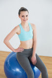 Mujer apta que se sienta en bola del ejercicio en estudio de la aptitud Foto de archivo