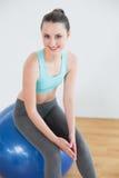 Mujer apta que se sienta en bola del ejercicio en estudio de la aptitud Fotografía de archivo