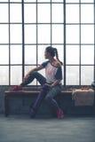 Mujer apta que se sienta en el banco del gimnasio del desván que mira hacia fuera la ventana Foto de archivo
