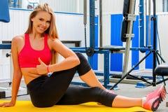 Mujer apta que se sienta en el piso en el gimnasio Imagen de archivo libre de regalías