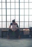 Mujer apta que se sienta en la reclinación del banco del gimnasio del desván, mirando abajo Fotografía de archivo
