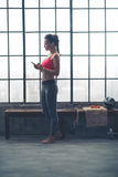 Mujer apta que selecciona música en el dispositivo en gimnasio del desván Imagen de archivo libre de regalías