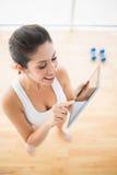 Mujer apta que usa la tableta que toma una rotura del entrenamiento Imagenes de archivo