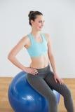 Mujer apta sonriente en bola del ejercicio en estudio de la aptitud Fotos de archivo