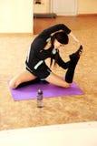 Mujer apta sonriente joven que estira en la estera de la yoga Imagenes de archivo