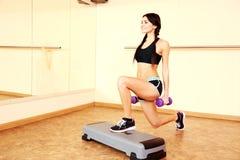 Mujer apta sonriente joven que hace ejercicios con los dumbells en tablero del paso Fotografía de archivo