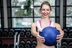 Mujer apta sonriente que ejercita con la bola de medicina Imágenes de archivo libres de regalías