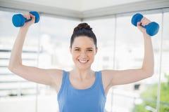Mujer apta sonriente que ejercita con pesas de gimnasia Foto de archivo libre de regalías