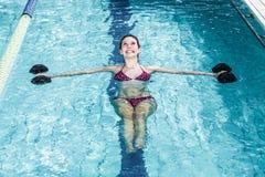 Mujer apta sonriente que hace aeróbicos de la aguamarina Foto de archivo