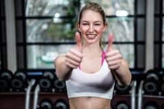 Mujer apta sonriente que muestra los pulgares para arriba Imágenes de archivo libres de regalías