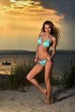 Mujer apta y deportiva en un traje de baño que se relaja en una playa en el verano fotografía de archivo libre de regalías
