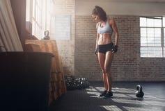 Mujer apta y joven que se coloca en gimnasio del crossfit Fotos de archivo libres de regalías