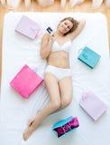 Mujer apuesta que miente en cama con los bolsos de compras Imágenes de archivo libres de regalías