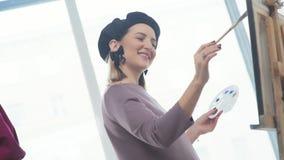 Mujer-artista en una boina, sosteniendo un cepillo y un dibujo, sonriendo metrajes