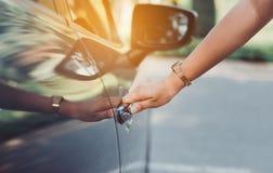Mujer ascendente cercana de las manos usando dominante de sistemas cerca del coche imagen de archivo