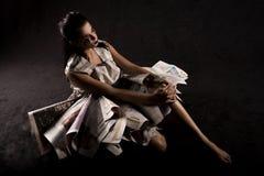 Mujer asentada con los periódicos Imagen de archivo libre de regalías
