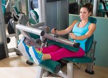 Mujer asentada gimnasio del ejercicio de la máquina del rizo de pierna fotos de archivo