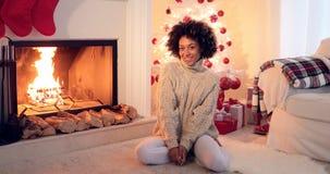 Mujer asentada por el árbol de navidad y los presentes blancos fotografía de archivo