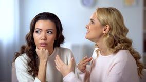 Mujer asiática aburrida que escucha su amigo molesto, uninvolved en la conversación imagen de archivo