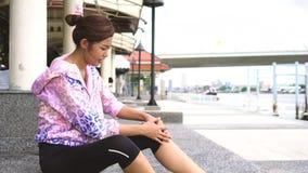 Mujer asiática adulta joven que tiene accidente del dolor común de rodilla en activar almacen de metraje de vídeo