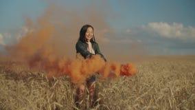 Mujer asiática alegre con la bomba de humo coloreado al aire libre almacen de metraje de vídeo