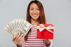 Mujer asiática alegre en el suéter que presenta el dinero y el regalo fotografía de archivo libre de regalías