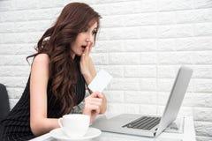 Mujer asiática asombrosamente cuando tarjeta de crédito del uso para las compras en línea Imagen de archivo libre de regalías
