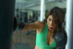 Mujer asiática atractiva atlética y apta joven del combatiente que perfora el bolso pesado con los guantes de boxeo en el gimnasi fotografía de archivo libre de regalías