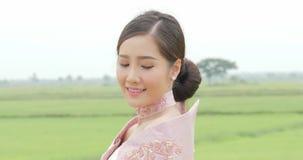 Mujer asiática atractiva en cabeza de torneado del traje asiático suroriental tradicional a la cámara y sonrisa en un fondo de a almacen de video
