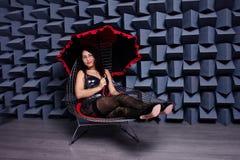 Mujer asiática atractiva hermosa en un pequeño vestido negro en una silla, MES imagen de archivo
