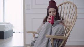 Mujer asiática atractiva hermosa que usa la tableta para mandar un SMS y leer mientras que se sienta en silla cuando relájese en  almacen de metraje de vídeo