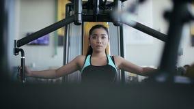 Mujer asiática atractiva joven en el gimnasio metrajes